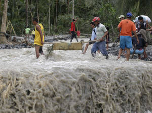 Photo - Residents cross a river with the body of a child after retrieving it from the flash flood-hit village of Andap, in New Bataan township, Compostela Valley in southern Philippines Wednesday Dec. 5, 2012, a day after the devastating Typhoon Bopha made landfall. Typhoon Bopha, one of the strongest typhoons to hit the Philippines this year, barreled across the country's south on Tuesday, killing scores of people while triggering landslides, flooding and cutting off power in two entire provinces. (AP Photo/Bullit Marquez)