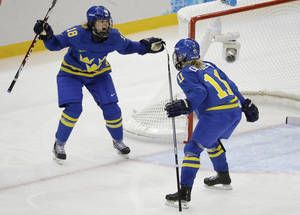 Photo - Cecilia Ostberg of Sweden (11) celebrates her goal against Germany with teammate Anna Borgqvist (18) during the third period of the 2014 Winter Olympics women's ice hockey game at Shayba Arena, Tuesday, Feb. 11, 2014, in Sochi, Russia. (AP Photo/Mark Humphrey)