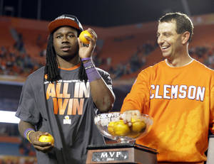 Photo - Clemson wide receiver and MVP of the game, Sammy Watkins, left, and head coach Dabo Swinney throw oranges into the crowd after Clemson defeated Ohio State 40-3 in the Orange Bowl NCAA college football game, Saturday, Jan. 4, 2014, in Miami Gardens, Fla. (AP Photo/Wilfredo Lee)