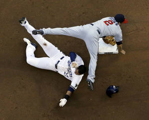 Photo - Minnesota Twins' Brian Dozier (2) leaps over Milwaukee Brewers' Carlos Gomez (27) at second to turn a double play on a ball hit by Khris Davis during the fourth inning of a baseball game, Monday, June 2, 2014, in Milwaukee. (AP Photo/Morry Gash)