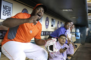 Photo - Houston Astros relief pitcher Jerome Williams, left, cheers as he and reporters watch the World Cup soccer match between the United States and Germany before the baseball game between the Astros and the Atlanta Braves Thursday, June 26, 2014, in Houston. (AP Photo/Pat Sullivan)