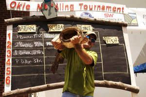 Photo - Scooter Bivins of Temple, one of the cast members of the cable television show Mudcats, holds up a flathead at the Okie Noodling Tournament in Pauls Valley. <strong>Photo provided</strong>