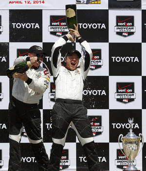 Photo - Brett Davern, right, celebrates after winning the Pro/Celebrity Grand Prix of Long Beach auto race with Al Unser, Jr. on Saturday, April 12, 2014, in Long Beach, Calif. Davern won the celebrity part of the race and Unser won the pro part. (AP Photo/Alex Gallardo)
