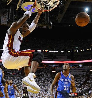 Photo -   Miami Heat power forward Chris Bosh (1) dunks as Oklahoma City Thunder small forward Kevin Durant (35) looks on during the first half of Game 3 of the NBA Finals basketball series, Sunday, June 17, 2012, in Miami. (AP Photo/Larry W. Smith, Pool)