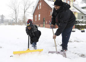 Photo - Keishard Hatcher, 6, left, helps his father Montez Gates, 29, shovel in front of their Monica Street home in Detroit after heavy snows covered the area Sunday Dec. 15, 2013. A pre-winter snowstorm continues to grip parts of Michigan, with accumulations already topping 9 inches in the state's southeastern corner. (AP Photo/Detroit Free Press, Mandi Wright)  DETROIT NEWS OUT;  NO SALES