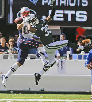 Photo - New York Jets free safety Antonio Allen (39) and New England Patriots' Rob Gronkowski (87) fight for control of the ball during the first half of an NFL football game Sunday, Oct. 20, 2013 in East Rutherford, N.J.  (AP Photo/Seth Wenig)