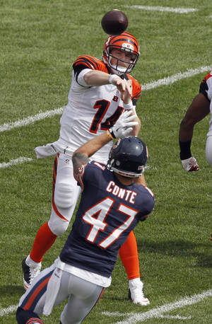 Photo - Cincinnati Bengals quarterback Andy Dalton passes under pressure from Chicago Bears safety Chris Conte (47) during the first half of an NFL football game, Sunday, Sept. 8, 2013, in Chicago. (AP Photo/Kiichiro Sato)