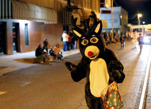 Photo - Right: Rudolph waves to people during a Christmas parade in El Reno on Thursday.
