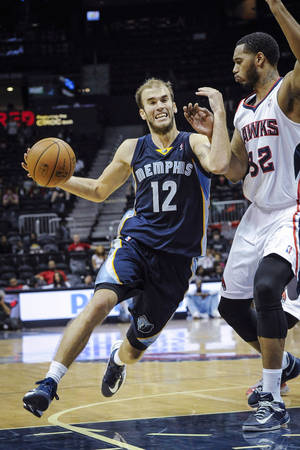 Photo - Memphis Grizzlies' Nick Calathes (12) drives against the defense of Atlanta Hawks forward Mike Scott (32) during the second half of an NBA preseason basketball game, Sunday, Oct. 20, 2013, in Atlanta. (AP Photo/ John Amis)