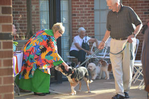 Photo - The Rev. Bertha Potts, senior minister, pets a dog walked by George Hedger Sept. 9 during the blessing of the animals at Edmond's First United Methodist Church. Photo by Ben Bigler, The Oklahoman <strong>Ben Bigler - The Oklahoman</strong>