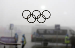 Photo - Olympic rings on a window are silhouetted against thick fog at the Laura Biathlon centre at the 2014 Winter Olympics, Monday, Feb. 17, 2014, in Krasnaya Polyana, Russia. The men's 15-kilometer mass-start biathlon race at the Sochi Olympics has been delayed due to fog, one day after the event had been called off for the same reason. (AP Photo/Felipe Dana)