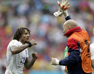 Photo - United States' Jermaine Jones, left, celebrates with a teammate after qualifying for the next World Cup round following their 1-0 loss to Germany during the group G World Cup soccer match between the USA and Germany at the Arena Pernambuco in Recife, Brazil, Thursday, June 26, 2014. (AP Photo/Julio Cortez)