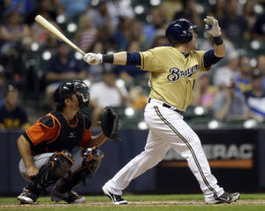 Photo - Milwaukee Brewers' Caleb Gindl, right, hits a walkoff home run during the 13th inning of a baseball game against the Miami Marlins, Sunday, July 21, 2013, in Milwaukee. (AP Photo/Morry Gash)