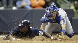 Photo -   Milwaukee Brewers' Nyjer Morgan, left, slides safely past Los Angeles Dodgers catcher A.J. Ellis during the 10th inning of a baseball game on Wednesday, April 18, 2012, in Milwaukee. The Brewers won 3-2. (AP Photo/Morry Gash)