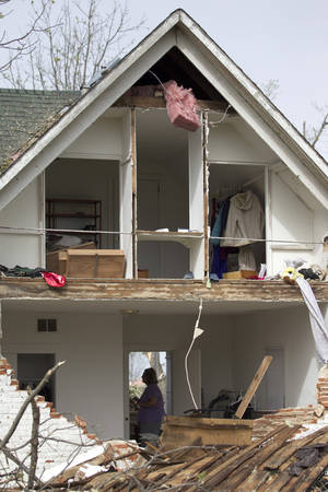 Photo - FILE - In this April 15, 2012 file photo, a woman is framed in the doorway of a damaged home in Thurman, Iowa, after it was destroyed by a tornado the night before. In 2012 many of the warnings scientists have made about global warming went from dry studies in scientific journals to real-life video played before our eyes. (AP Photo/Nati Harnik, File)