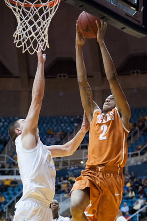 Photo - Texas' Demarcus Holland, right, drives to the basket as West Virginia's Nathan Adrian defends during the second half of an NCAA college basketball game, Monday, Jan. 13, 2014, in Morgantown, W.Va. Texas won 80-69. (AP Photo/Andrew Ferguson)