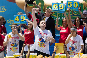 Photo - Joey Chestnut, center, wins the Nathan's Famous Fourth of July International Hot Dog Eating contest with a total of 69 hot dogs and buns, alongside Tim Janus, left, and Matt Stonie, right, Thursday, July 4, 2013 at Coney Island, in the Brooklyn borough of New York. (AP Photo/John Minchillo)