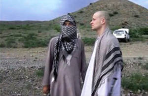 Photo - FILE - In this file image taken from video obtained from Voice Of Jihad Website, which has been authenticated based on its contents and other AP reporting, Sgt. Bowe Bergdahl, right, stands with a Taliban fighter in eastern Afghanistan. The Taliban said Friday, June 6, 2014, that Bergdahl was treated well during the five years they held him captive and was even allowed to play soccer with the men holding him. (AP Photo/Voice Of Jihad Website via AP video, File)