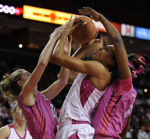 Photo - Maryland's Alicia DeVaughn, center, is sandwiched between Clemson's Jordan Gaillard, left, and Nyilah Jamison-Myers in the first half of an NCAA women's college basketball game, Sunday, Feb. 9, 2014, in College Park, Md. (AP Photo/Gail Burton)