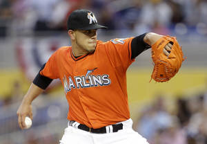 Photo - Miami Marlins starting pitcher Jose Fernandez throws during the first inning of an opening day baseball game against the Colorado Rockies, Monday, March 31, 2014, in Miami. (AP Photo/Lynne Sladky)