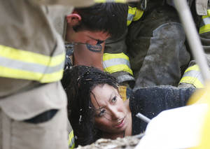 Photo - Jennifer Doan, a teacher at Plaza Towers elementary school, is pulled out from under tornado debris at the school in Moore on May 20. <strong>Sue Ogrocki - AP</strong>