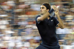 Photo -   Roger Federer, of Switzerland, returns a shot to Bjorn Phau, of Germany, during a match at the U.S. Open tennis tournament, Thursday, Aug. 30, 2012, in New York. (AP Photo/Darron Cummings)