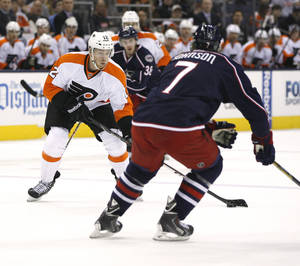 Photo - Philadelphia Flyers' Michael Raffl (12) prepares to shoot past Columbus Blue Jackets' Jack Johnson (7) during the first period of an NHL hockey game on Saturday, Dec. 21, 2013, in Columbus, Ohio. (AP Photo/Mike Munden)