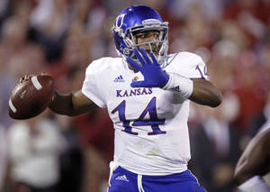 Photo -   FILE - In this Oct. 20, 2012, file photo Kansas quarterback Michael Cummings throws a pass against Oklahoma in the fourth quarter of an NCAA college football game in Norman, Okla. Weis is sticking with his young quarterback when Kansas plays Texas on Saturday. (AP Photo/Sue Ogrocki, File)