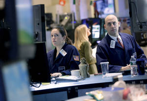 Photo - Traders work on the floor at the New York Stock Exchange in New York, Monday, Dec. 31, 2012. World stocks cooled off Monday Jan. 7, 2013 as some investors sold shares to lock in profits following recent rallies.  (AP Photo/Seth Wenig)