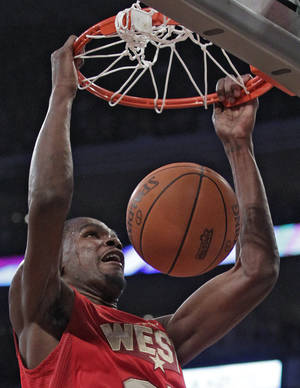 Photo - West's Kevin Durant, of the Oklahoma City Thunder, dunks during the first half of the NBA basketball All-Star Game on Sunday, Feb. 20, 2011, in Los Angeles. (AP Photo/Jae C. Hong)