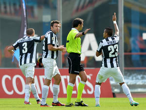 Photo -   Juventus players Arturo Vidal, of Chile, right, Andrea Barzagli, second from left, and Giorgio Chiellini, argue with referee Gervasoni after Catania's Gonzalo Bergessio, of Argentina, not pictured, scored a goal (which was then disallowed) during the Serie A soccer match between Catania and Juventus at the Angelo Massimino stadium in Catania, Italy, Sunday, Oct. 28, 2012. Juventus won 1-0. (AP Photo/Carmelo Imbesi)