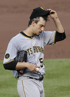 Photo - Pittsburgh Pirates starting pitcher Charlie Morton adjusts his cap before an at-bat against Baltimore Orioles' Steve Pearce in the sixth inning in the first baseball game of a doubleheader on Thursday, May 1, 2014, in Baltimore. Pearce drove in a run during his at-bat and Morton was relieved. (AP Photo/Patrick Semansky)