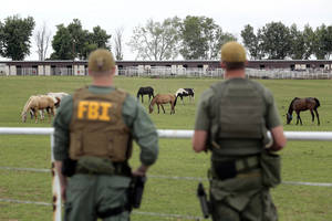 Photo - In this June 12 file photo, FBI agents overlook a horse ranch under investigation in Lexington. AP Photo