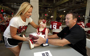 Photo - Christa Lorton, Bixby,  and 15-month-old daughter Alexis, obtain an autograph from head coach Bob Stoops during the Meet the Sooners event inside Gaylord Family/Oklahoma Memorial Stadium at the University of Oklahoma on Saturday, Aug. 4, 2012, in Norman, Okla.  Photo by Steve Sisney, The Oklahoman
