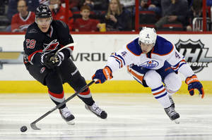 Photo - Edmonton Oilers' Taylor Hall (4) poke the puck away from Carolina Hurricanes' Alexander Semin (28), of Russia, during the second period of an NHL hockey game in Raleigh, N.C., Sunday, March 16, 2014. (AP Photo/Karl B DeBlaker)