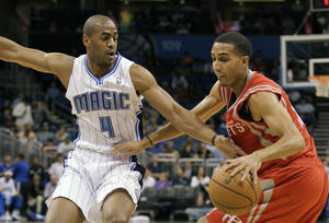 Photo - Orlando Magic's Arron Afflalo (4) reaches in to try to steal the ball from Houston Rockets' Kevin Martin, right, during the first half of an NBA preseason basketball game, Friday, Oct. 26, 2012, in Orlando, Fla. (AP Photo/John Raoux)  ORG XMIT: DOA106