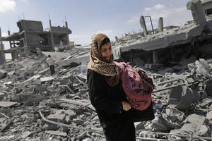 Photo - A Palestinian woman carries her belongings past the rubble of houses destroyed by Israeli strikes in Beit Hanoun, northern Gaza Strip, Saturday, July 26, 2014. Thousands of Gaza residents who had fled Israel-Hamas fighting streamed back to devastated border areas during a lull Saturday, and were met by large-scale destruction: scores of homes were pulverized, wreckage blocked roads and power cables dangled in the streets. (AP Photo/Lefteris Pitarakis)