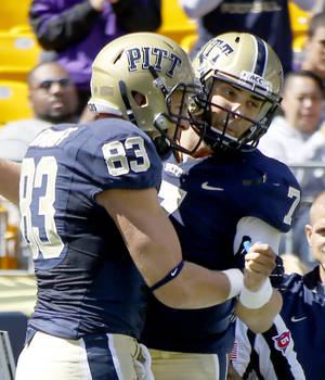 Photo - Pittsburgh tight end Scott Orndoff (83) is greeted by quarterback Tom Savage (7) after catching a touchdown pass from Savage in the first quarter of an NCAA football game against New Mexico on Saturday, Sept. 14, 2013, in Pittsburgh. (AP Photo/Keith Srakocic)