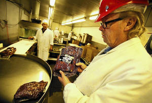 Photo - BURBANK, CA - MARCH 28, 2014: Jerry Haines, right, General Manager at R.C. Provisions in Burbank on March 28, 2014 holds packaged Pastrami ready for shipping as beef prices are at record highs because of thinning cattle herds decimated by drought, that has now trickled down the supply chain and hurt suppliers like R.C. Provisions. The nearly 50-year-old company supplies L.A. famed delis such as Langer's with pastrami, corned beef and roast beef as well as chili for Tommy's and Pinks. The soaring cost of raw materials has driven their profit margins to 1% and less. (Al Seib / Los Angeles Times)