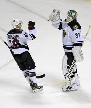 Photo - Minnesota Wild defenseman Jared Spurgeon (46) celebrates with goaltender Josh Harding (37) after third period of an NHL hockey game against the Buffalo Sabres in Buffalo, N.Y., Monday, Oct. 14, 2013. Minnesota won 2-1.  (AP Photo/Gary Wiepert)