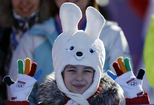Photo - A girl wears a hat in the shape of the Sochi Winter Olympics mascot while watching the men's snowboard slopestyle qualifying at the Rosa Khutor Extreme Park ahead of the 2014 Winter Olympics, Thursday, Feb. 6, 2014, in Krasnaya Polyana, Russia.  (AP Photo/Andy Wong)