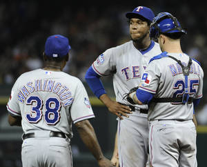 Photo -   Texas Rangers pitcher Neftali Feliz, center, looks off as manager Ron Washington (38) heads to mound to take him out of the game as catcher Mike Napoli (25) stands beside him in the fifth inning of an interleague baseball game against the Houston Astros, Friday, May 18, 2012, in Houston. (AP Photo/Pat Sullivan)