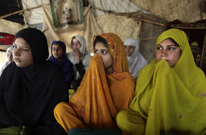 Photo - Pakistani women and girls listen to their teacher Mohammad Shiraz, 24, not pictured, during a three hours daily class, teaching illiterate women and children how to read Urdu alphabet and verses of the holy Quran, in a makeshift tent on the outskirts of Islamabad, Pakistan, Tuesday, April 2, 2013. According to the United Nations only 40 percent of Pakistani girls 15 or younger are literate in Pakistan. (AP Photo/Muhammed Muheisen)
