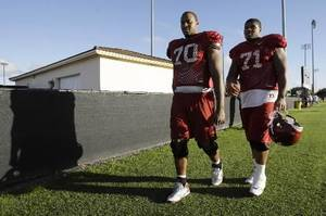 Photo - Oklahoma offensive linemen Cory Brandon (70) and  Trent  Williams (71) walk off the field after football practice at Barry University in Miami Shores, Fla, Tuesday, Jan. 6, 2009. Oklahoma will play Florida in the BCS Championship NCAA college football game on Thursday, Jan. 8. (AP Photo/ Lynne Sladky)