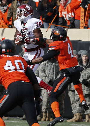Photo - Oklahoma State cornerback Justin Gilbert (4) breaks up a pass intended for Oklahoma wide receiver Jaz Reynolds (16) in the first quarter of an NCAA college football game in Stillwater, Okla., Saturday, Dec. 7, 2013. (AP Photo/Sue Ogrocki)