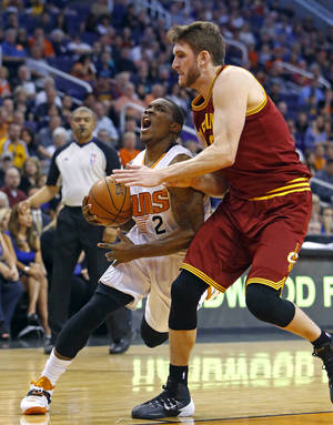 Photo - Phoenix Suns guard Eric Bledsoe (2) works against Cleveland Cavaliers center Spencer Hawes (32) during the first half of their NBA basketball game, Wednesday, March 12, 2014, in Phoenix, Ariz. (AP Photo/The Arizona Republic, David Kadlubowski) MARICOPA COUNTY OUT; MAGS OUT; NO SALES.