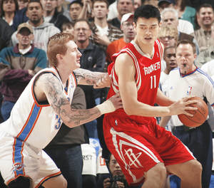 Photo - Houston's Yao Ming, right, tries to get past the Thunder's Robert Swift during Monday's game at the Ford Center. PHOTO BY NATE BILLINGS, THE OKLAHOMAN