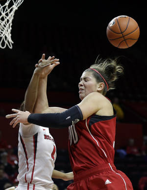 Photo - Rutgers guard Briyona Canty (4) blocks a shot by Louisville forward Sara Hammond (00) during the first half of an NCAA college basketball game Tuesday, Jan. 28, 2014, in Piscataway, N.J. (AP Photo/Mel Evans)