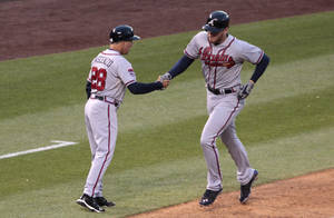 Photo - Atlanta Braves third base coach Doug Dascenzo (28) greets Braves' Freddie Freeman as Freeman rounds third base on his solo home run in the fourth inning of a baseball game in Denver on Tuesday, June 10, 2014. (AP Photo/Joe Mahoney)