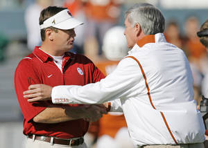 Photo - OU head coach Bob Stoops, left, and Texas head coach Mack Brown shake hands before the Red River Rivalry college football game between the University of Oklahoma Sooners (OU) and the University of Texas Longhorns (UT) at the Cotton Bowl in Dallas, Texas, Saturday, Oct. 17, 2009. Photo by Nate Billings, The Oklahoman